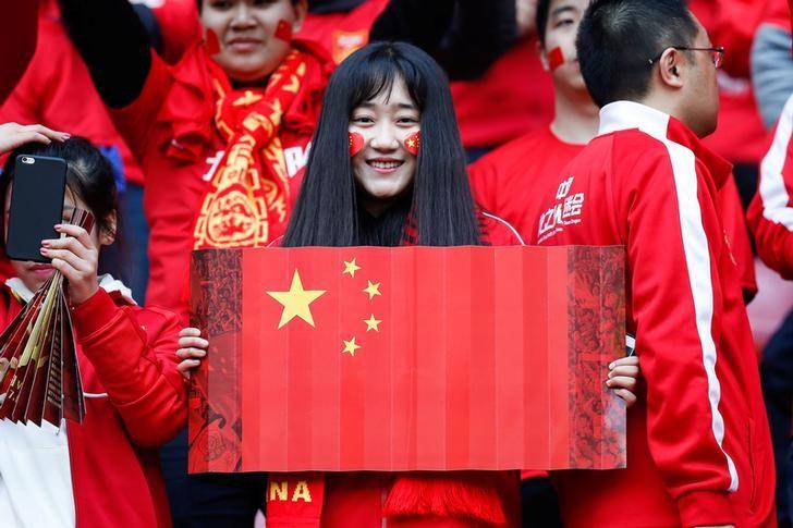 A fan holds a Chinese national flag inside Helong Stadium ahead of a 2018 FIFA World Cup qualifier match between China and South Korea in Changsha, Hunan province, China, March 23, 2017. REUTERS/Stringer