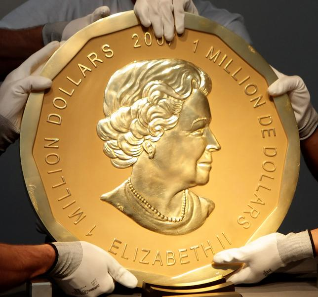 FILE PHOTO - Picture taken in Vienna, Austria on June 25, 2010 shows experts of an Austrian art forwarding company holding one of the world's largest gold coins, a 2007 Canadian $ 1,000,000 ''Big Maple Leaf''.  REUTERS/Heinz-Peter Bader/File Photo