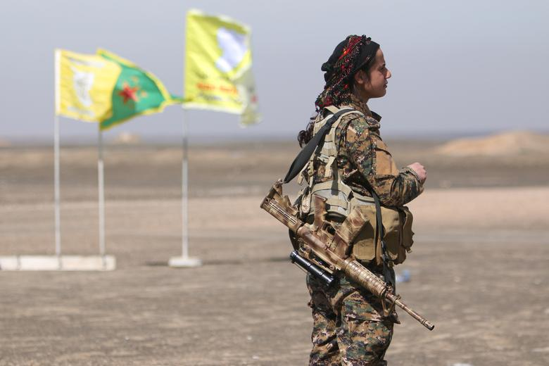 A Syrian Democratic Forces (SDF) female fighter stands with her weapon east of Raqqa city, Syria.   REUTERS/Rodi Said