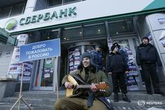 """A member of the Azov civil corp sits next to a placard reading, """"Welcome back to Russia"""" during a protest in front of a branch of Sberbank, which protesters say supports Russian """"aggression"""" in Eastern Ukraine, in Kiev, Ukraine January 30, 2017.  REUTERS/Valentyn Ogirenko - RTSY1V7"""