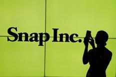 FILE PHOTO: A woman stands in front of the logo of Snap Inc. on the floor of the New York Stock Exchange (NYSE) while waiting for Snap Inc. to post their IPO, in New York City, NY, U.S. March 2, 2017. REUTERS/Lucas Jackson/Files
