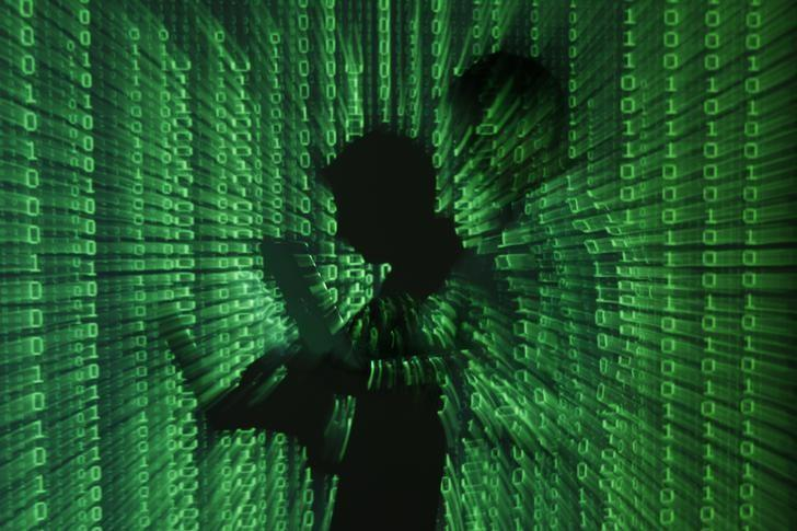 An illustration picture shows a projection of binary code on a man holding a laptop computer, in an office in Warsaw June 24, 2013. REUTERS/Kacper Pempel/File Photo