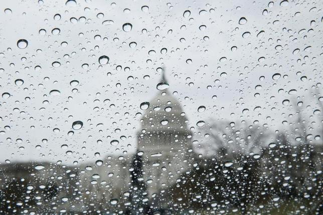 3月27日、ホワイトハウスは、旧来の難解な予算関連法令への対応に苦しんでいる。写真は米首都ワシントンで24日、雨の窓越しに見える連邦議会議事堂(2017年 ロイター/Jim Bourg)