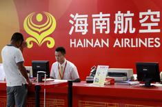 FILE PHOTO: A customer (L) stands in front of a counter of Hainan Airlines at an airport in Haikou, Hainan province, China, July 29, 2014. REUTERS/Stringer/File Photo