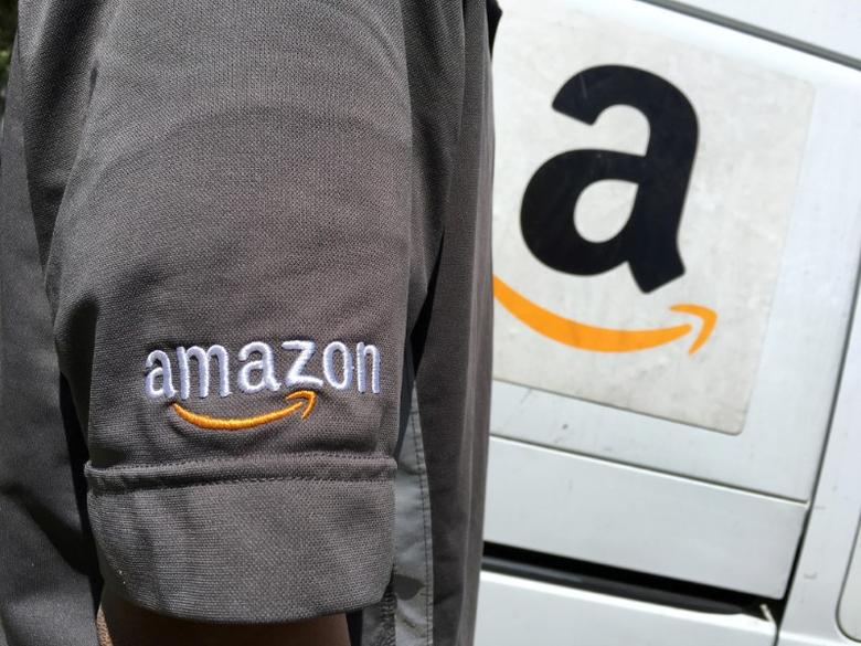 FILE PHOTO: An Amazon.com Inc driver stands next to an Amazon delivery truck in Los Angeles, California, U.S., May 21, 2016. REUTERS/Lucy Nicholson/File photo