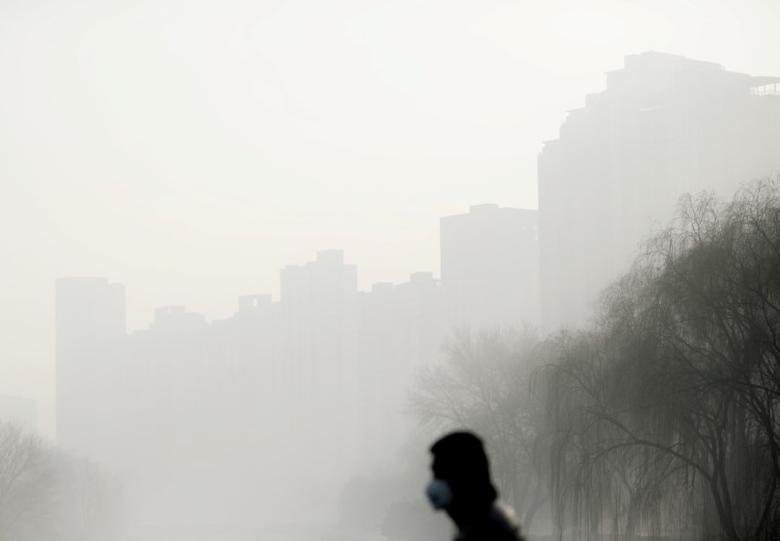A person walks on a street wearing a mask during a haze day in Beijing, China, January 4, 2017. Picture taken January 4, 2017. REUTERS/Stringer