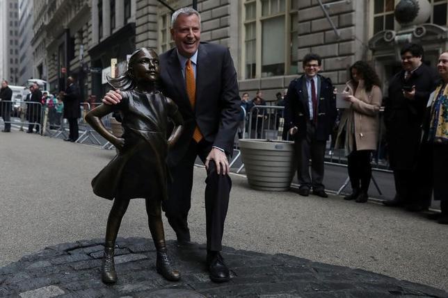 3月27日、国際女性デーの前日の今月7日、ウォール街の象徴である雄牛の銅像「チャージング・ブル」の前に設置され、わずか3週間で多くのファンを得た「恐れ知らずの少女」の像が、少なくとも今後11カ月間継続展示されることになった。写真は少女像とビル・デブラシオNY市長(2017年 ロイター/Shannon Stapleton)