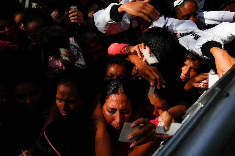Women queues on the street as they try to buy diapers outside a pharmacy in Caracas, Venezuela March 18, 2017. REUTERS/Carlos Garcia Rawlins
