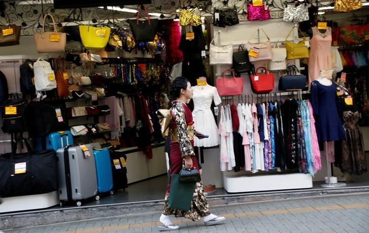 FILE PHOTO: A woman in a kimono walks past a shop in a shopping district in Tokyo, Japan March 23, 2017.   REUTERS/Kim Kyung-Hoon/File Photo