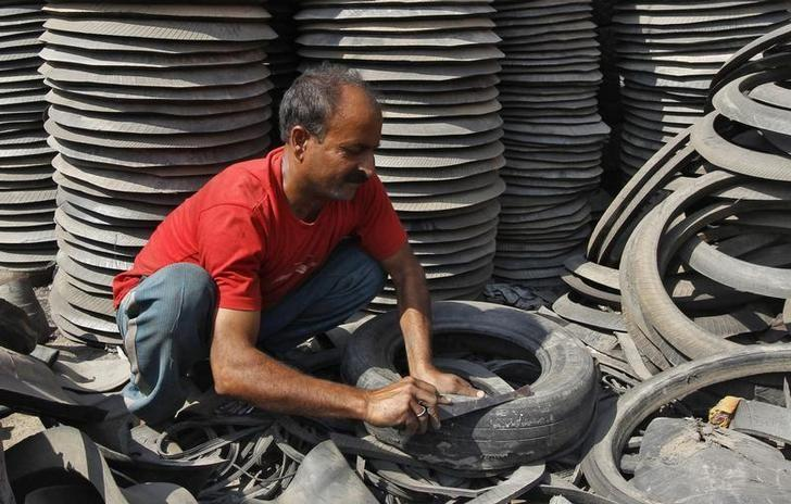 A worker dismantles a worn-out rubber tyre for recycling at a workshop in Srinagar August 19, 2011. REUTERS/Danish Ismail/Files