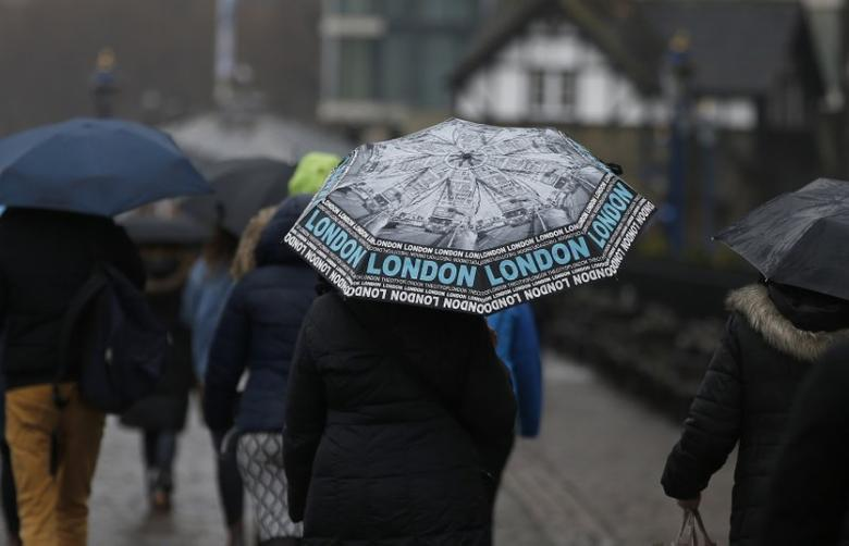Tourists carrying umbrellas walk in the rain during a spell of wet weather, next to The Tower of London, in London, Britain January 15, 2017. REUTERS/Peter Nicholls