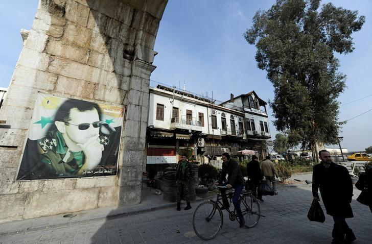 People walk past a picture of Syria's President Bashar al-Assad at Bab Sharqi entrance, near the Jobar district of Damascus, Syria, January 5, 2017. REUTERS/Omar Sanadiki/Files