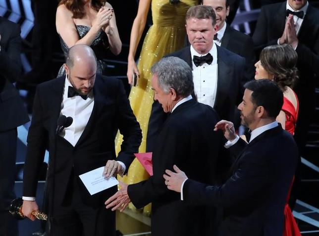 89th Academy Awards - Oscars Awards Show - Hollywood, California, U.S. - 26/02/17 - Martha Ruiz (R, in red) and Brian Cullinan (upper R) of PricewaterhouseCoopers confer on stage after the Best Picture was mistakenly awarded to ''La La Land'' instead of ''Moonlight''. REUTERS/Lucy Nicholson