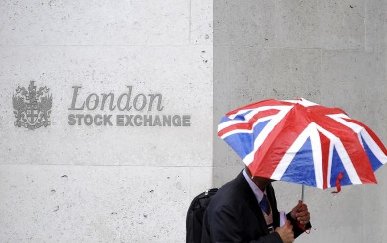 FILE PHOTO: A worker shelters from the rain under a Union Flag umbrella as he passes the London Stock Exchange in London, Britain, October 1, 2008.  REUTERS/Toby Melville/File Photo