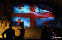 Люди смотрят на проекцию флага Грузии в Тбилиси 21 июля 2016 года. Рост валового внутреннего продукта (ВВП) Грузии ускорился в январе-феврале текущего года до 4,8 процента с 1,7 процента годом ранее, сообщила Национальная статистическая служба страны в четверг. REUTERS/David Mdzinarishvili