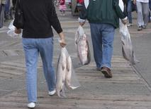 People carry salmon after purchasing it from fishers on the docks in Steveston, British Columbia September 1, 2010. REUTERS/Andy Clark
