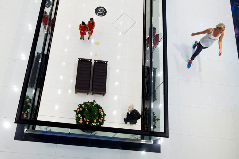 FILE PHOTO: People walk through the Mall of Berlin shopping centre during its opening night in Berlin, September 24, 2014.   REUTERS/Thomas Peter/File Photo