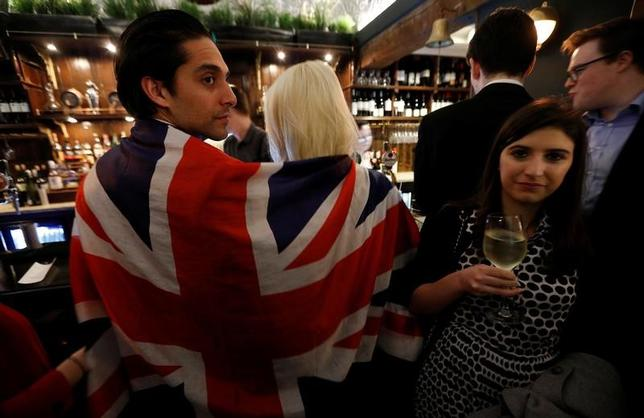 3月30日、英国政府は欧州連合(EU)法を国内法に置き換える計画を公表した。手始めにEUの法体系全体を英国法に転換する。企業が抱くEU離脱後の不透明感を払拭する狙いがある。写真は英国のEU離脱手続きが正式に始まったことを祝うイベントに集まった人々。ロンドンのパブで29日撮影(2017年 ロイター/Peter Nicholls)