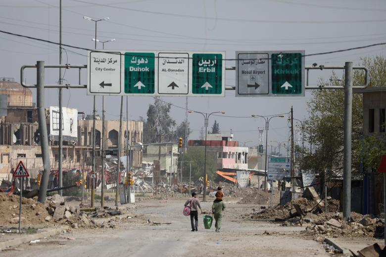 Civilians carrying their goods walk along a street in an area controlled by Iraqi forces in Mosul, Iraq, March 30, 2017. REUTERS/Andres Martinez Casares
