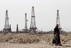 Мужчина с ребенком у нефтяного месторождения Румайла в Басре. 26 января 2016 года. Добыча нефти ОПЕК в марте может уменьшиться третий месяц подряд благодаря усилению сокращения производства ОАЭ и вынужденному снижению его объёмов в Нигерии и Ливии, показали расчёты Рейтер. REUTERS/Essam Al-Sudani