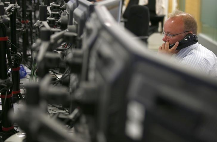 A trader at ETX Trading speaks on the telephone at their offices in London.  REUTERS/Peter Nicholls