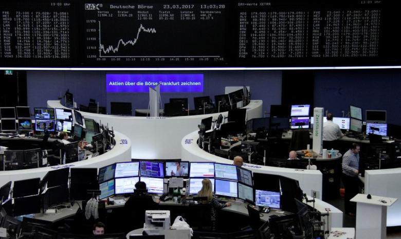 Traders work at their desks in front of the German share price index, DAX board, at the stock exchange in Frankfurt, Germany, March 23, 2017. REUTERS/Staff/Remote