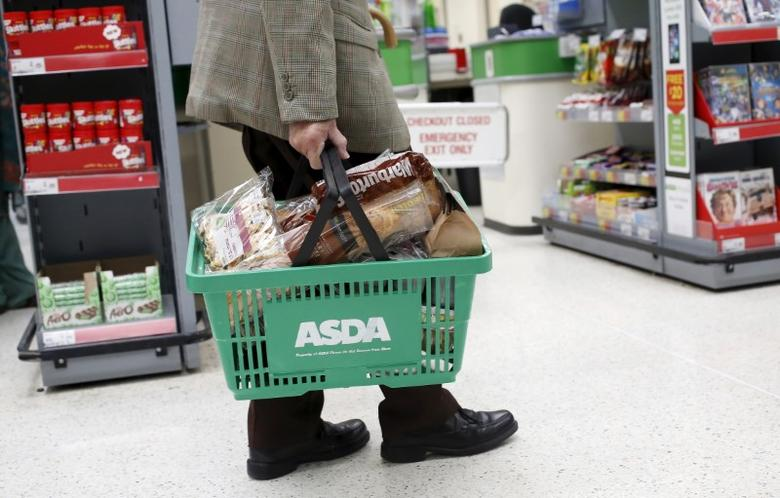 A man carries a shopping basket in an Asda store in northwest London, Britain in this August 18, 2015 file photo. Asda is expected to give a Q4 trading update this week.    REUTERS/Suzanne Plunkett/Files