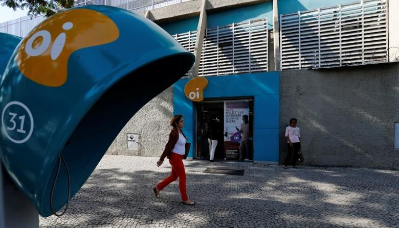 People walk in front of the headquarters of the Brazil's largest fixed-line telecoms group Oi, in Rio de Janeiro, Brazil, June 22, 2016. REUTERS/Sergio Moraes - RTX2HN8N