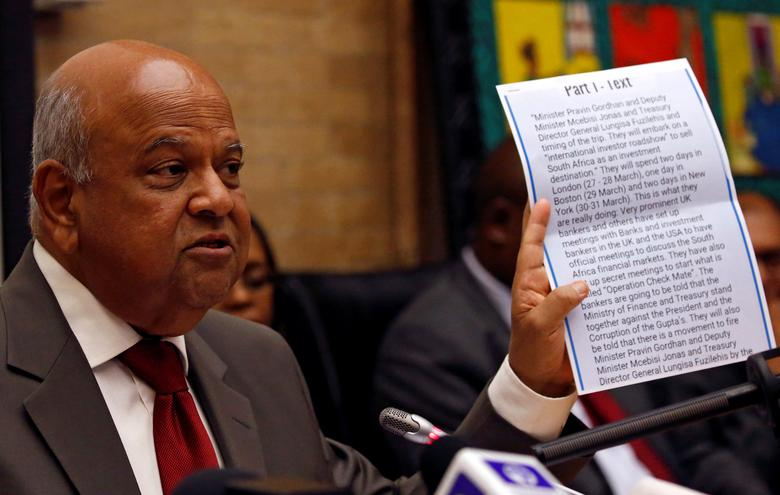 Pravin Gordhan holds a copy of an intelligence report that President Jacob Zuma used as justification to fire him, during a media briefing at their offices in Pretoria, South Africa, March 31,2017. REUTERS/Siphiwe Sibeko