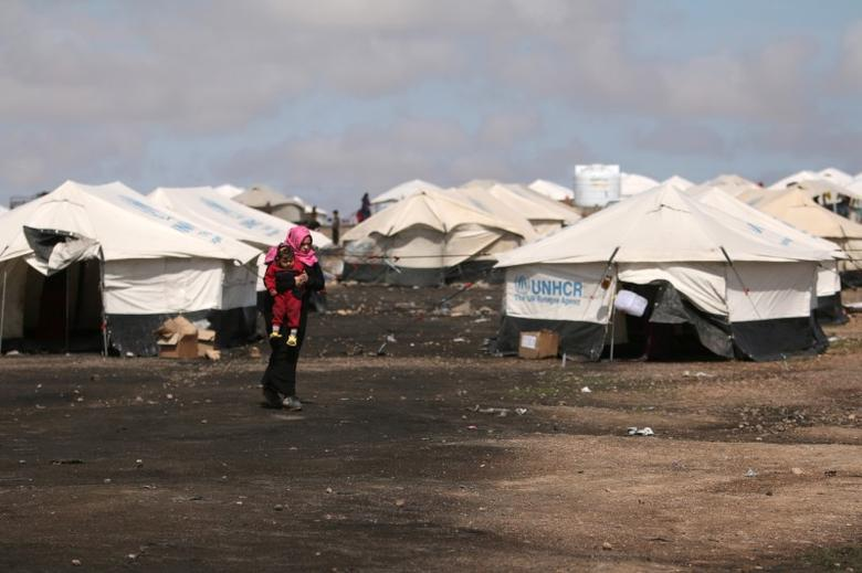 An internally displaced woman who fled Raqqa city walks carrying a child near tents in a camp in Ain Issa, Raqqa Governorate, Syria April 1, 2017. REUTERS/Rodi Said