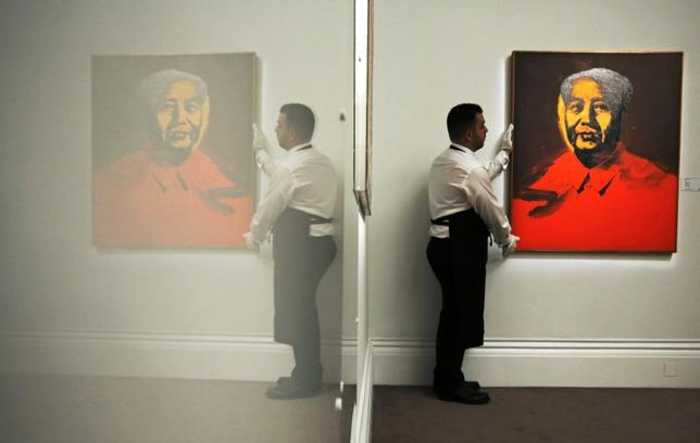 FILE PHOTO - An employee poses with artist Andy Warhol's artwork ''Mao'' at Sotheby's auction house in London January 29, 2014. REUTERS/Luke MacGregor