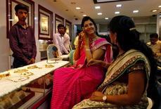 Женщина примеряет золотые украшения в ювелирном магазине в Мумбаи. 28 октября 2016 года. Спрос на золото в Индии на минувшей неделе вырос благодаря фестивальным торжествам и укреплению рупии, тогда как в других азиатских странах покупатели не спешат на фоне роста цен. REUTERS/Danish Siddiqui