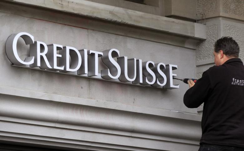 A worker uses a cordless screwdriver to fix the logo of Swiss bank Credit Suisse at a branch office in Zurich February 4, 2013. Credit Suisse will present its annual results for 2012 on February 7.  REUTERS/Arnd Wiegmann