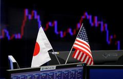FILE PHOTO - National flags of Japan and the U.S. are seen in front of a monitor showing a graph of the Japanese yen's exchange rate against the U.S. dollar at a foreign exchange trading company in Tokyo, Japan, January 23, 2017.    REUTERS/Toru Hanai/File Photo