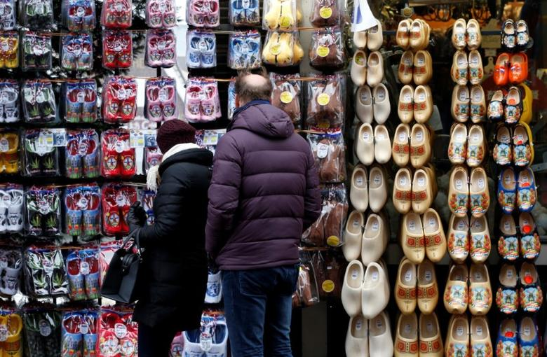 A couple watches clogs displayed in a tourist shop at the port of Volendam near Amsterdam, Netherlands February 11, 2017.   REUTERS/Francois Lenoir