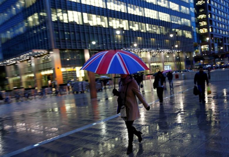 FILE PHOTO: Workers walk in the rain at the Canary Wharf business district in London, Britain November 11, 2013.     REUTERS/Eddie Keogh/File Photo
