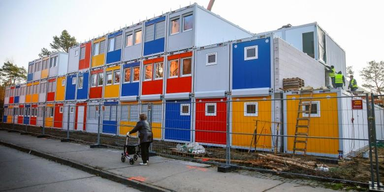 FILE PHOTO - Workers fix containers at a construction site for a refugee centre to house asylum seekers in the Koepenick district of Berlin, Germany November 27, 2014.    REUTERS/Hannibal Hanschke/File Photo