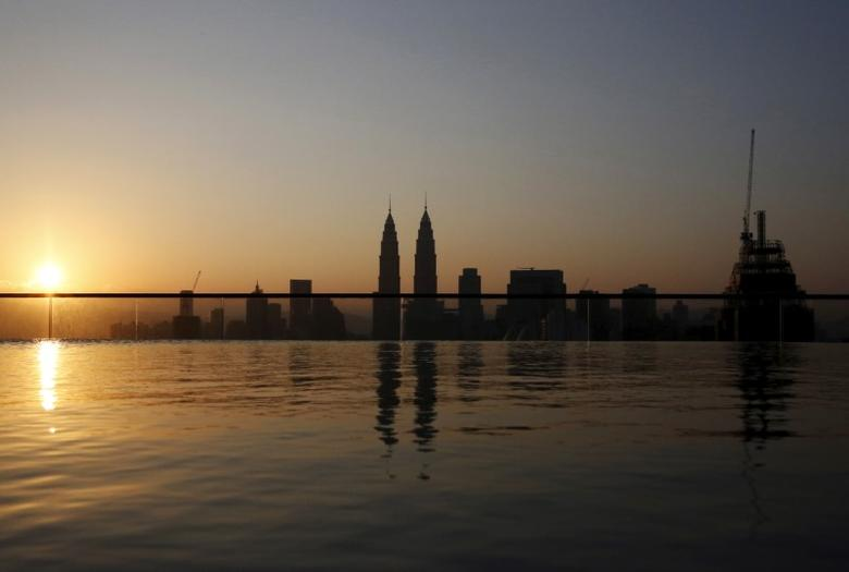 The Petronas Towers are reflected in a swimming pool as the sun rises over Kuala Lumpur, Malaysia, March 29, 2016.  REUTERS/Olivia Harris