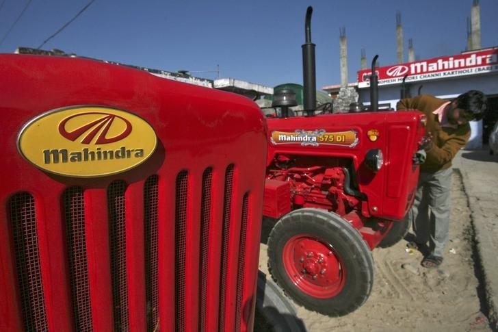 A worker cleans a Mahindra tractor outside its showroom on the outskirts of Jammu November 28, 2013. REUTERS/Mukesh Gupta/Files