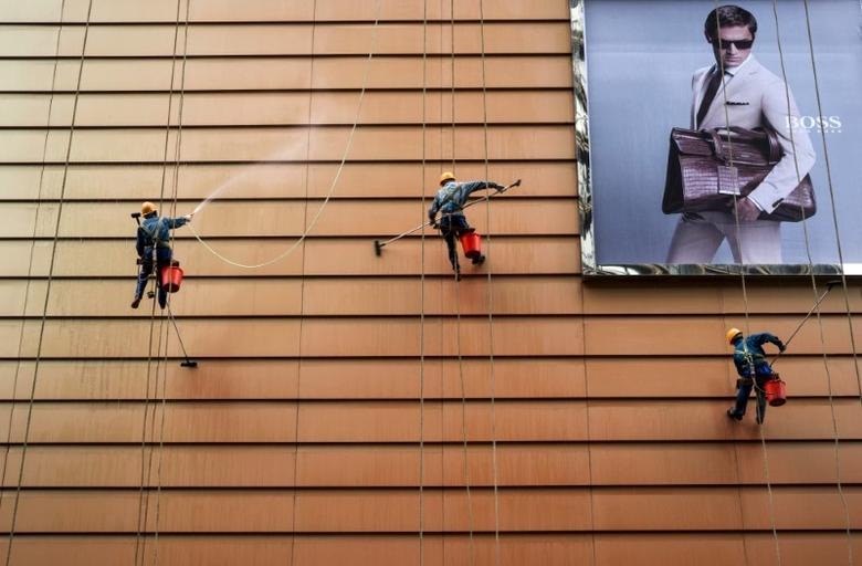 Workers clean the exteriors of a building next to an advertisement in Wuxi, Jiangsu province, China, May 23, 2015. REUTERS/Stringer/File Photo