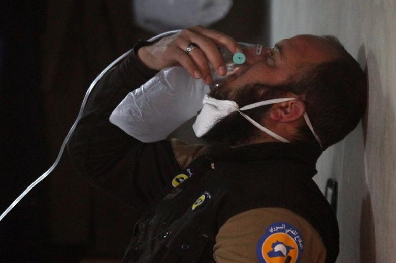 A civil defence member breathes through an oxygen mask, after what rescue workers described as a suspected gas attack in the town of Khan Sheikhoun in rebel-held Idlib, Syria April 4, 2017. REUTERS/Ammar Abdullah     TPX IMAGES OF THE DAY