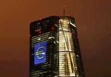 """FILE PHOTO: The headquarters of the European Central Bank (ECB) are illuminated with a giant euro sign at the start of the """"Luminale, light and building"""" event in Frankfurt, Germany, March 12, 2016.   REUTERS/Kai Pfaffenbach/File Photo"""