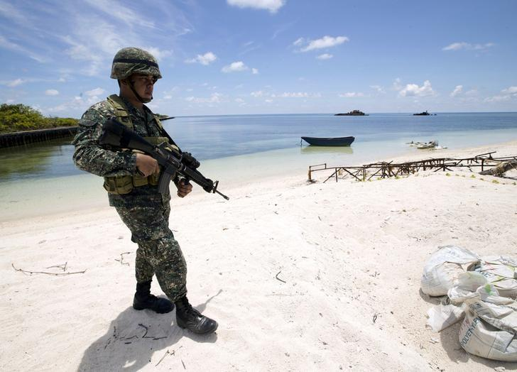 FILE PHOTO: A Filipino soldier patrols at the shore of Pagasa island (Thitu Island) in the Spratly group of islands in the South China Sea, west of Palawan, Philippines, May 11, 2015.        REUTERS/Ritchie B. Tongo/Pool/File Photo/File Photo