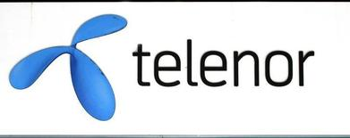The Telenor logo hangs outside one of their stores in Stockholm October 26, 2007. REUTERS/Bob Strong (SWEDEN)