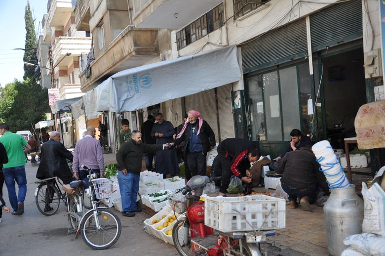 People shop along a street in the city of Homs, Syria in this handout picture provided by SANA on April 7, 2017. SANA/Handout via REUTERS
