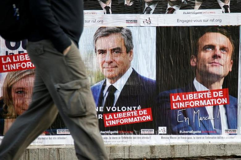 Campaign posters of 2017 presidential election candidates Francois Fillon of the Republicans political party and Emmanuel Macron (R) head of the political movement En Marche !, (Onwards!) in Paris, France, April 5, 2017. REUTERS/Charles Platiau