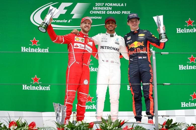 Formula One - F1 - Chinese Grand Prix - Shanghai, China - 09/04/17 - Winner Mercedes driver Lewis Hamilton of Britain celebrates on the podium with Ferrari driver Sebastian Vettel of Germany and Red Bull Racing driver Max Verstappen of the Netherlands after the Chinese Grand Prix at the Shanghai International Circuit. REUTERS/Aly Song