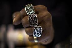 Мужчина демонстрирует кольца с символом доллара в Нью-Йорке 6 ноября 2014 года. Доллар начал неделю у трёхнедельного максимума к корзине основных валют, после того, как чиновник американского Федрезерва подтвердил приверженность регулятора политике повышения ставок, однако геополитические опасения инвесторов ограничили рост. REUTERS/Mike Segar/File Photo