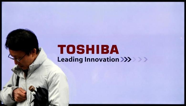 A man walks past a Toshiba Corp logo displayed on one of its television sets in Tokyo, Japan, November 26, 2015. REUTERS/Toru Hanai/File Photo