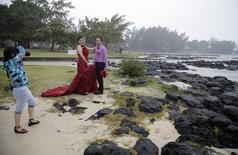 A Chinese couple from Yunnan pose for a photographer during a wedding photo session at the Cap Malheureux beach on the Indian Ocean island Mauritius, August 5, 2015. REUTERS/Jacky Naegelen